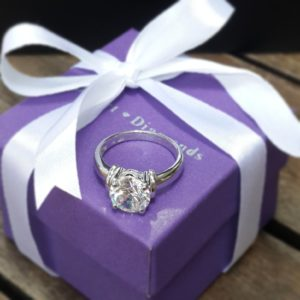 Desert Diamonds purple gift box wrapped in ribbon with solitaire diamond ring