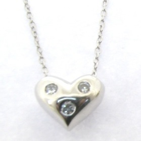 solid silver heart pendant with 3 diamonds embeded on a 18 inch gold chaine