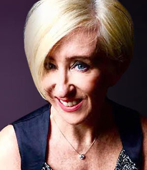 head shot of Sally Cowley owner of Desert Diamonds Jewelry with aubergine background