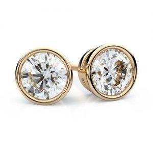 a pair of gold bezel set diamond stud earrings